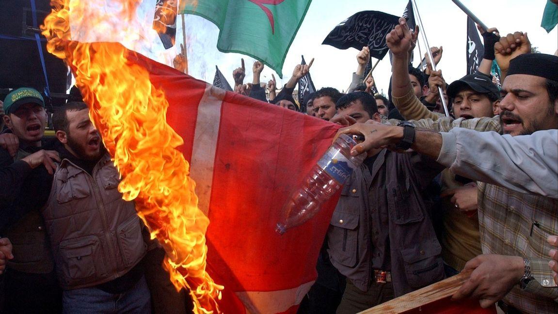 En dansk flagga bränns under en demonstration mot de danska Muhammedteckningarna i det palestinska flyktinglägret Ein-el-Hilweh i södra Libanon i februari 2006. Foto: Mohammed Zaatari/AP/TT.