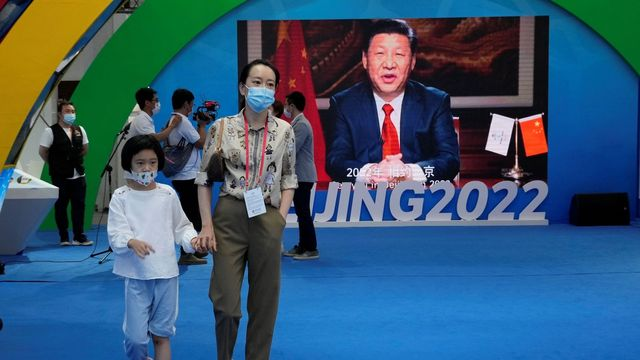 A woman and child wearing masks pass by a screen displaying Chinese President Xi Jinping during the China International Fair for Trade in Services (CIFTIS) in Beijing Sunday, Sept. 5, 2021. An avalanche of changes launched by China's ruling Communist Party has jolted everyone from tech billionaires to school kids. Photo: Ng Han Guan/AP/TT